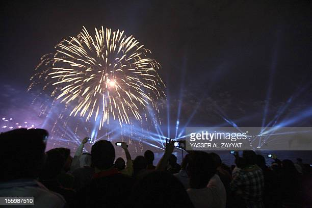 Kuwaitis take photographs as fireworks light the sky near the Kuwait Towers during celebrations marking the Gulf state's 50th anniversary of its...