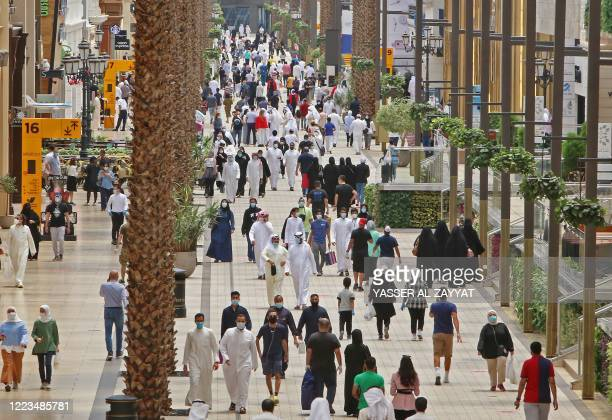 Kuwaitis wearing face masks walk inside the re-opened Avenues Mall, the country's largest shopping centre, on June 30, 2020 in Kuwait City after...