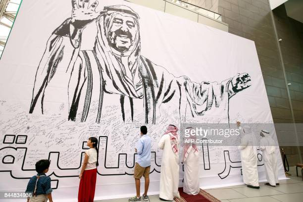 Kuwaitis write remarks on a banner bearing the image of their Emir Sheikh Sabah AlAhmad AlJaber AlSabah at the Avenue Mall in Kuwait City on...