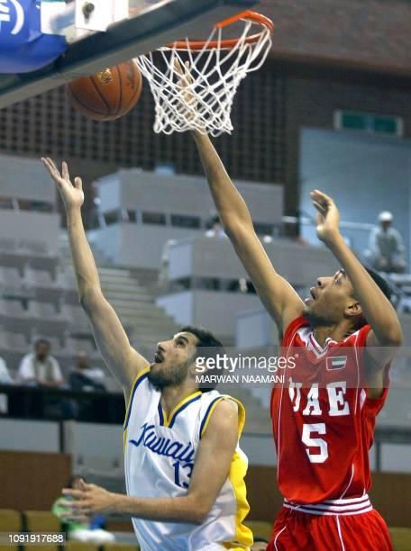 Kuwait's Hamad alShemmari scores as the United Arab Emirates' Mubarak Salem tries to defend during their basketball game at Geumjong Gymnasium during...