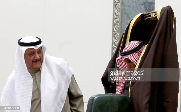 Kuwait's National Assembly Speaker Marzouq alGhanim puts on a 'bisht' traditional cloak as Deputy Speaker Essa AlKandari looks on during a parliament...