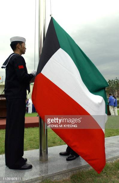 Kuwait's national flag is hoisted at the 14th Asian Games Athletes' Village 27 September 2002 during a flagraising ceremony to welcome the Kuwaiti...