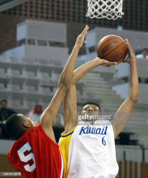 Kuwait's Sulaiman alTabakh attempts to score for his country in the United Arab Emirates as Mubarak Salem tries to stop him during the two countries...
