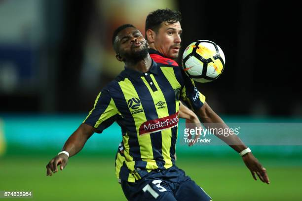 Kwabena Appiah of the Mariners contests the ball with his Adelaide United opponent during the round seven A-League match between the Central Coast...
