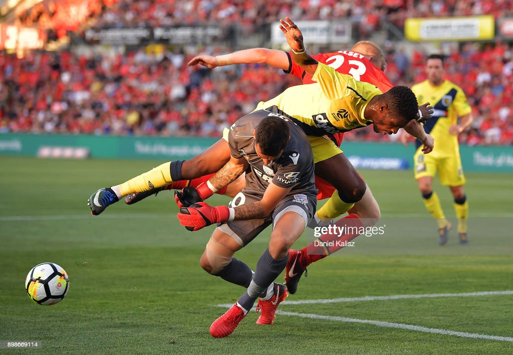 Kwabena Appiah-Kubi of the Mariners and Jordan Elsey of United collide with United goalkeeper Paul Izzo during the round 12 A-League match between Adelaide United and the Central Coast Mariners at Coopers Stadium on December 26, 2017 in Adelaide, Australia.