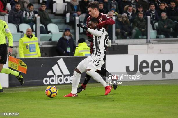 Kwadwo Asamoah and Daniele Baselli compete for the ball during the Italian Cup quarterfinal between Juventus FC and Torino FC at Allianz Stadium on...