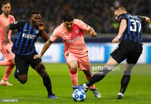 Kwadwo Asamoah of Inter Milan and Milan Skriniar of Inter Milan vie for the ball with Luis Suarez of Barcelona during the Group B match of the UEFA...