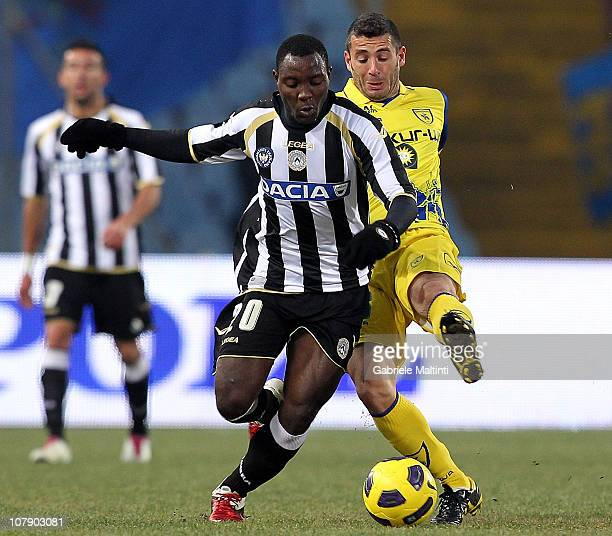 Kwadwo Asamoah of Udinese Calcio battles for the ball with Mariano Bogliacino of AC Chievo Verona during the Serie A match between Udinese and Chievo...