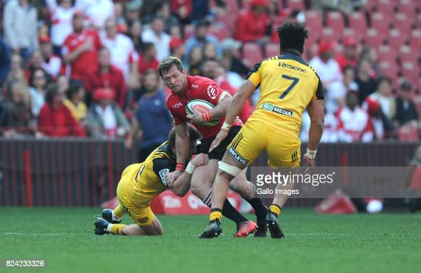 Kwagga Smith of Lions is tackled by TJ Perenara and Beauden Barrett of Hurricanes during the Super Rugby Semi Final match between Emirates Lions and...