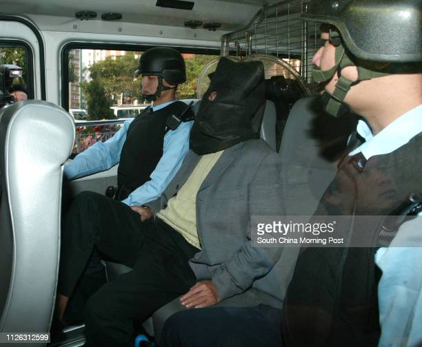 Kwai Pinghung Hong Kong's mostwanted armed robber facing charges of possession of arms and ammunition without a licence is escorted into court by...