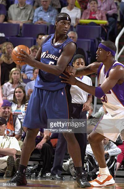 Kwame Brown of the Washington Wizards looks to play the ball against Amare Stoudemire during the game on March 29 2004 at America West Arena in...