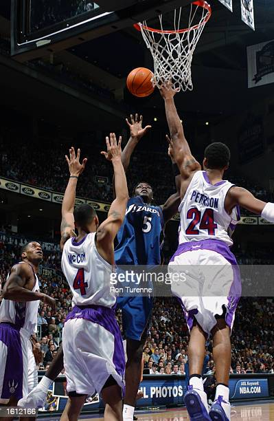 Kwame Brown of the Washington Wizards puts up a jumper over Morris Peterson and Jelani McCoy of the Toronto Raptors during the game at Air Canada...