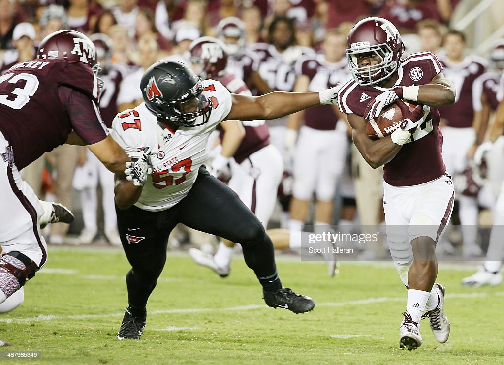 Kwame Etwi #22 of the Texas A&M Aggies runs with the ball in front of Joshua Posley #57 of the Ball State Cardinals in the second half of their game at Kyle Field on September 12, 2015 in College Station, Texas.