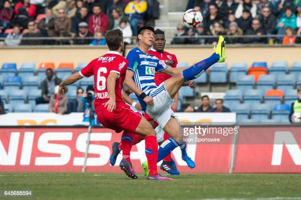 Kwang Ryong Pak vies with Paulo Ricardo Ferreira and Joaquim Adao during the Swiss Super League match between FC LausanneSport and FC Sion at Stade...