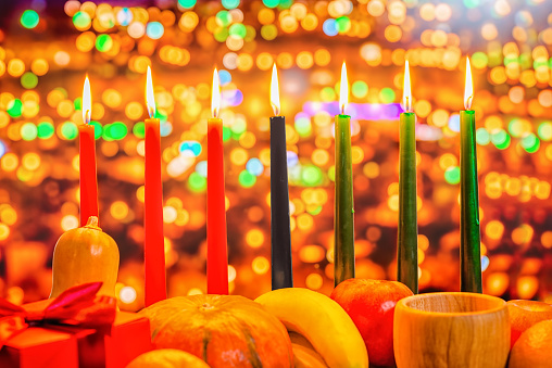 Kwanzaa celebration concept with seven candles red, black and green, gift box, pumpkin, bowl and fruit on light blur bokeh background, close up 816429236