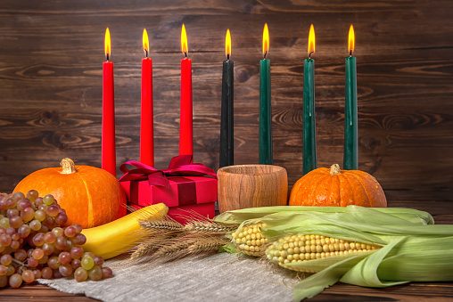 Kwanzaa festival concept with seven candles red, black and green, gift box, pumpkins, ears of wheat, grapes, corns, banana, bowl and fruits on wooden background, close up 879222820