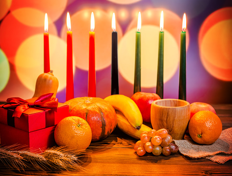 Kwanzaa festive concept with seven candles red, black and green, gift box, pumpkin, bowl and fruit on light blur bokeh background 843318510