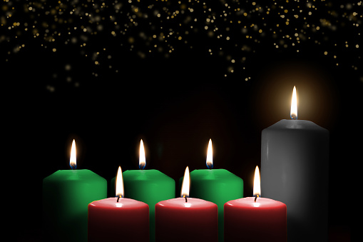 Kwanzaa for African-American cultural holiday celebration with candle light of seven candle sticks in black, green, red symbolising 7 principles of African Heritage (Nguzo Saba) 1186803879