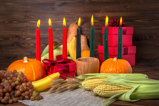 Kwanzaa holiday concept with candles red, black and green, gift box, pumpkins, ears of wheat, grapes, corns, banana, bowl and fruits on wooden background, close up 1090482672