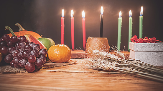 Kwanzaa holiday concept with decorate seven candles red, black and green, gift box, pumpkin,corn and fruit on wooden desk and background. 1186963052