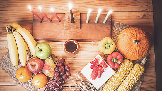 Kwanzaa holiday concept with decorate seven candles red, black and green, gift box, pumpkin,corn and fruit on wooden desk and background. 1186963061