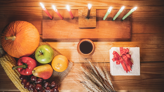 Kwanzaa holiday concept with decorate seven candles red, black and green, gift box, pumpkin,corn and fruit on wooden desk and background. 1190087295