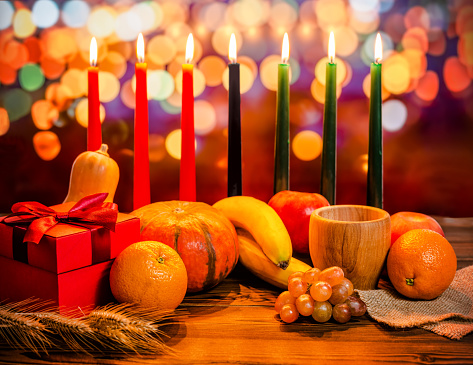Kwanzaa holiday concept with decorate seven candles red, black and green, gift box, pumpkin, bowl and fruit on light blur bokeh background 843318546