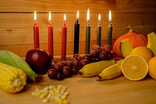 Kwanzaa holiday concept with decorate seven candles red, black and green, gift box, pumpkin,corn and fruit on wooden desk and background. 889627696