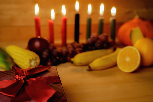 Kwanzaa holiday concept with decorate seven candles red, black and green, gift box, pumpkin,corn and fruit on wooden desk and background. 889627698