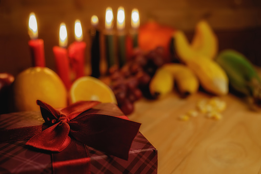Kwanzaa holiday concept with decorate seven candles red, black and green, gift box, pumpkin,corn and fruit on wooden desk and background. 889627708