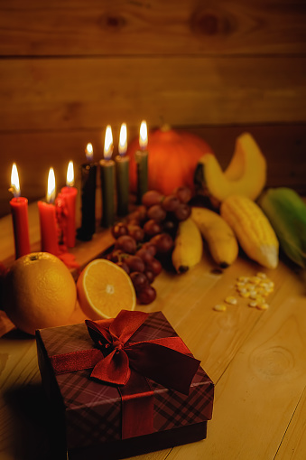 Kwanzaa holiday concept with decorate seven candles red, black and green, gift box, pumpkin,corn and fruit on wooden desk and background. 889627712