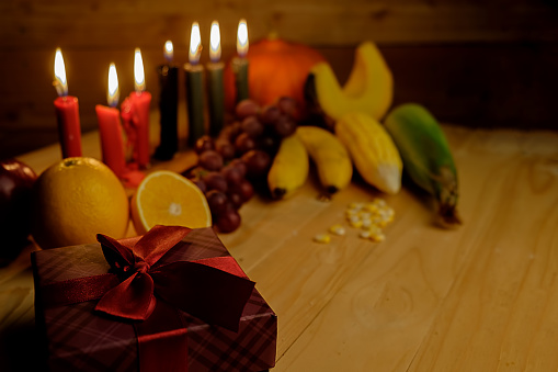 Kwanzaa holiday concept with decorate seven candles red, black and green, gift box, pumpkin,corn and fruit on wooden desk and background. 889629304