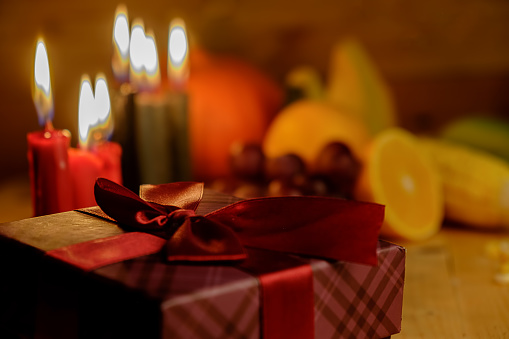 Kwanzaa holiday concept with decorate seven candles red, black and green, gift box, pumpkin,corn and fruit on wooden desk and background. 889629668