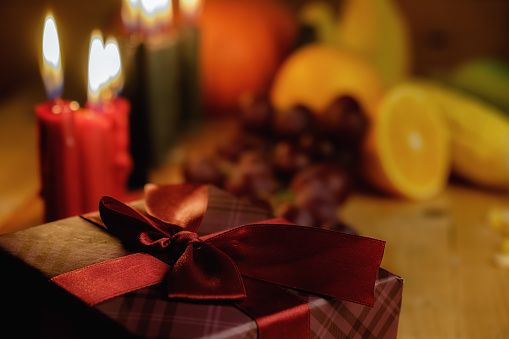 Kwanzaa holiday concept with decorate seven candles red, black and green, gift box, pumpkin,corn and fruit on wooden desk and background. 889629704