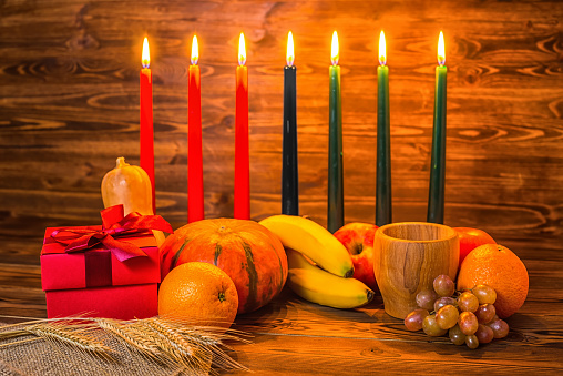 Kwanzaa holiday concept with traditional lit candles, gift box, pumpkins, ears of wheat, grapes, orange, banana, bowl and fruits on wood background 816429242