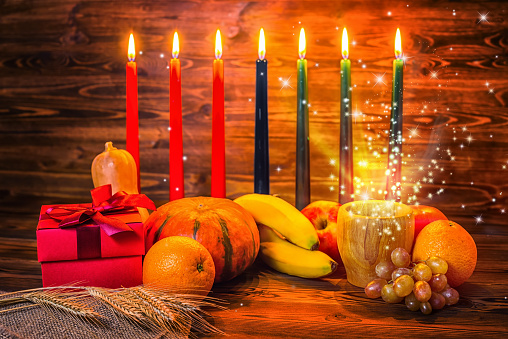 Kwanzaa holiday concept with traditional lit candles, gift box, pumpkins, ears of wheat and miracle magic light on wood background 900603878