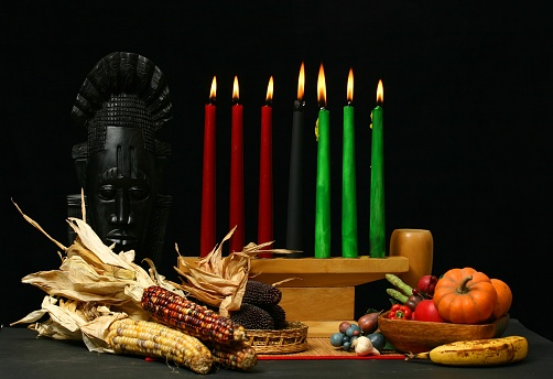 Kwanzaa table setting with candle and dried corn cobs 145119985