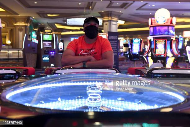 Kwasi Tripp of Tennessee wears a mask as he plays at a sociallydistanced electronic table game for roulette at Mandalay Bay Resort and Casino after...