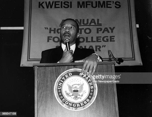 Kweisi Mfume holding a microphone and standing at a podium with a United States Congress seal 1991