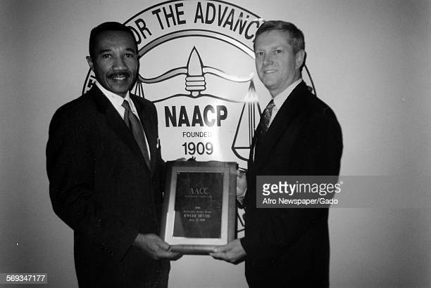 Kweisi Mfume holding an award from the National Association for the Advancement of Colored People where he served as President/CEO 1987