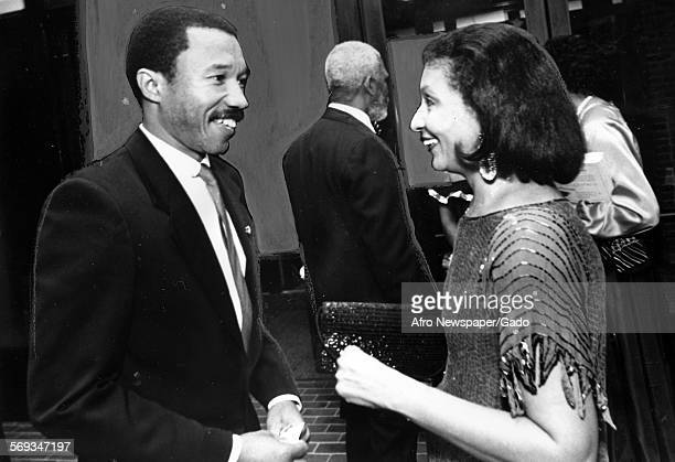 Kweisi Mfume speaking with a woman at a formal event 1987
