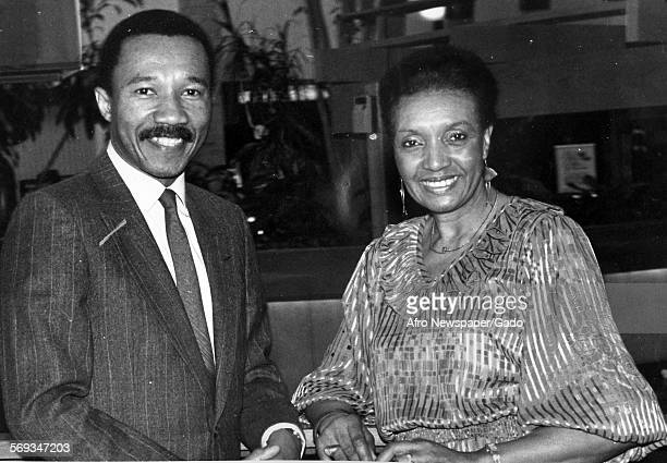 Kweisi Mfume wearing a suit sitting at a table with a woman 1987