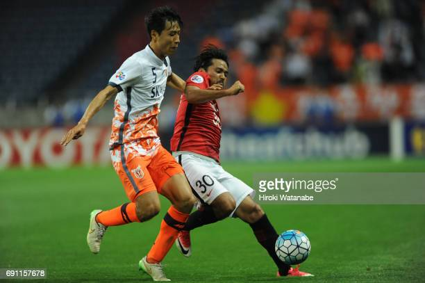 Kweon Hanjin of Jeju United FC and Shinzoh Koroki of Urawa Red Diamonds compete for the ball during the AFC Champions League Round of 16 match...