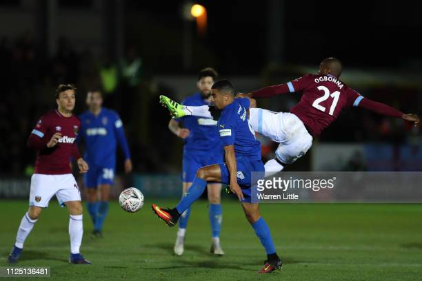Kwesi Appiah of AFC Wimbledon is challenged by Angelo Ogbonna of West Ham United during the FA Cup Fourth Round match between AFC Wimbledon and West...
