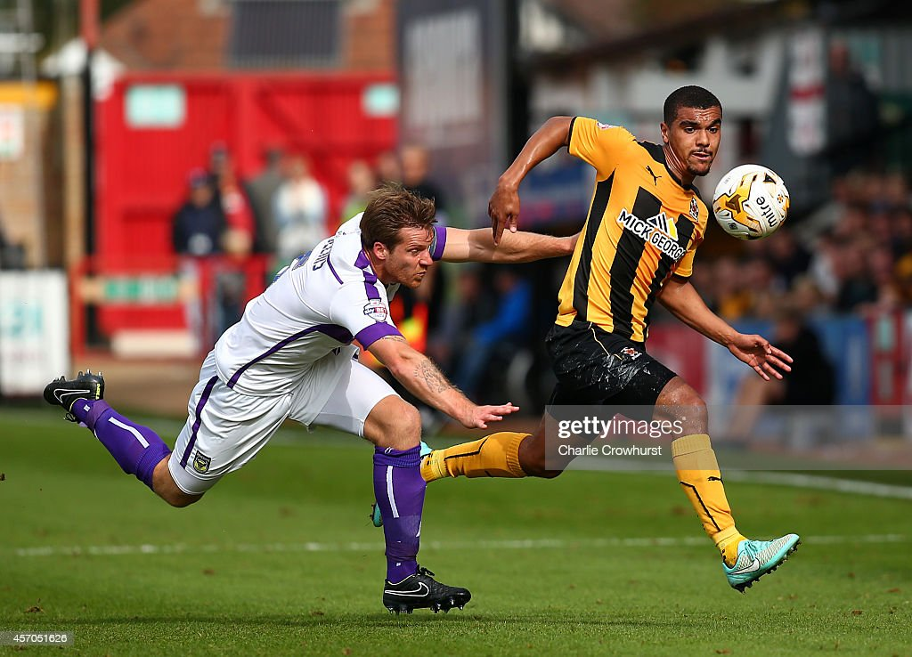 Kwesi Appiah (R) of Cambridge breaks away from Johnny Mullins of Oxford during the Sky Bet League Two match between Cambridge United and Oxford United at The Abbey Stadium on October 11, 2014 in Cambridge, England.