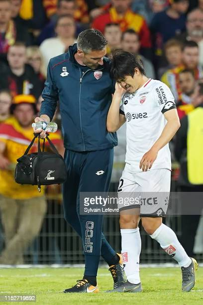 Kwon Chang-hoon of Dijon reaces medical attention after an injury during the French L1-L2 first leg play-off football match between Racing Club of...