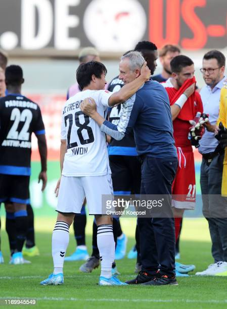 Kwon Chang-Hoon of SC Freiburg and Christian Streich, Manager of SC Freiburg celebrate victory during the Bundesliga match between SC Paderborn 07...
