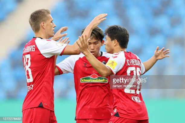 Kwon Chang-Hoon of SC Freiburg celebrates with his team mates after scoring his team's first goal during the DFB Cup first round match between SV...