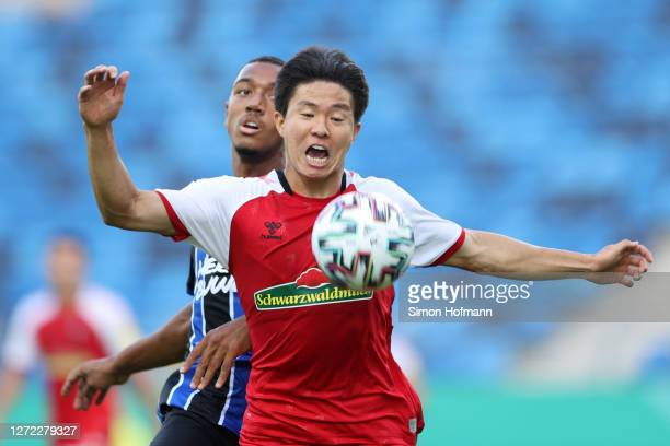 Kwon Chang-Hoon of SC Freiburg is challenged by Anton-Leander Donkor of SV Waldhof Mannheim during the DFB Cup first round match between SV Waldhof...