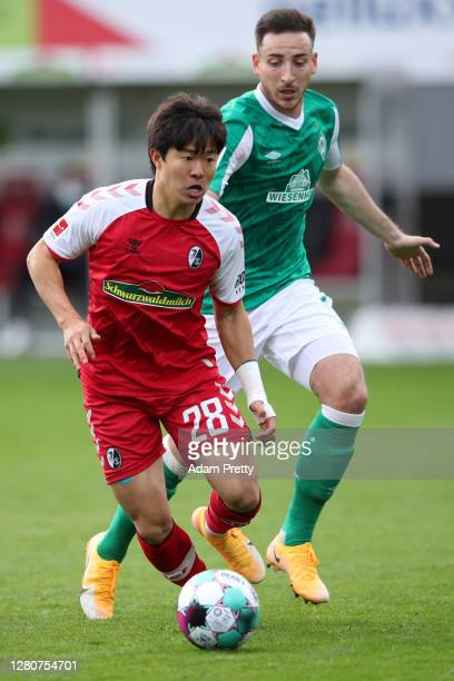 Kwon Chang-Hoon of SC Freiburg runs with the ball under pressure from Kevin Moehwald of Werder Bremen during the Bundesliga match between Sport-Club...